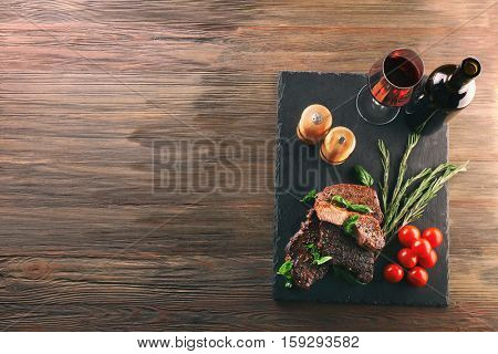 Delicious steak with tomatoes and herbs on wooden background