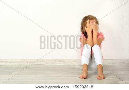 Crying little girl on floor in empty room