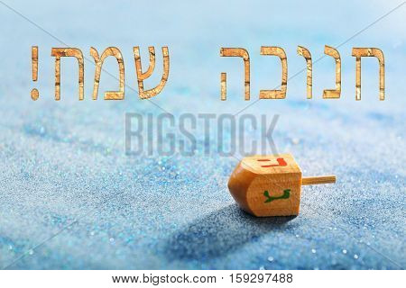 Wooden dreidel for Hanukkah on sparkling background. Hanukkah celebration concept. Text HAPPY HANUKKAH in Hebrew
