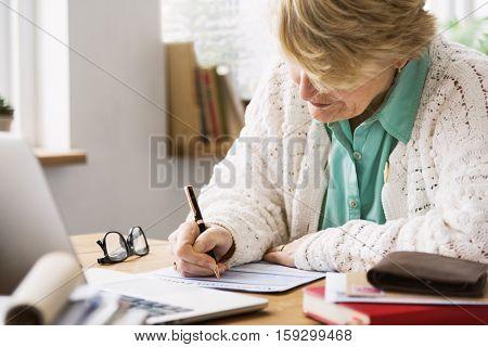 Senior Woman Filling Application Form Documents Concept