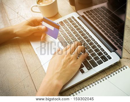 Businessman hand holding credit card and use laptop vintage tone.