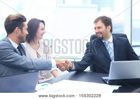 Business colleagues sitting at a table during a meeting with two