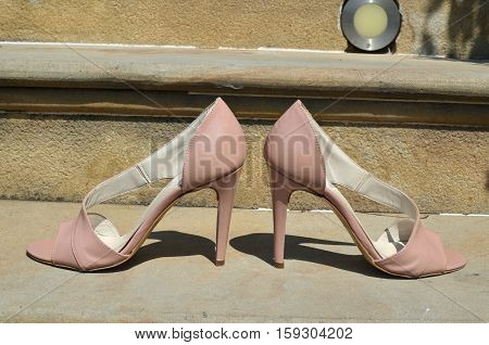 Pair of nude look elegant sandals on stone stairs