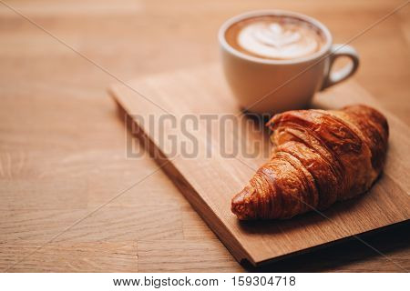 Cappuccino with beautiful latte art and croissant on wooden background on the table. Perfect breacfast in the morning. Rustic style.