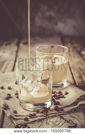 CPouring coffee liqueur in glasses with ice and beans, wood background, copy space
