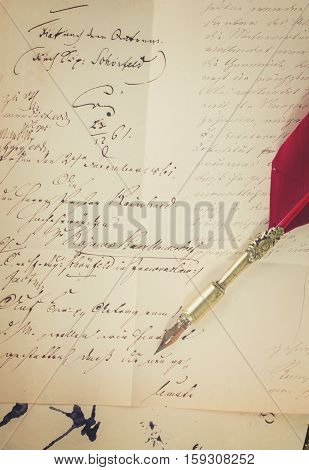 feather pen on old paper with antique letter , retro toned
