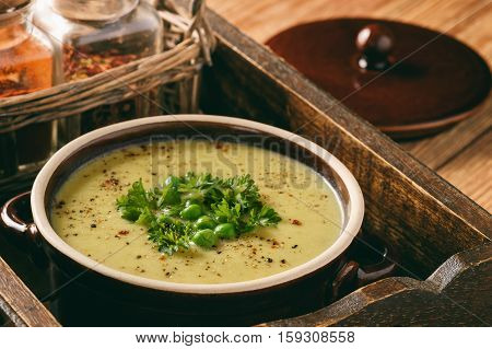 Cream soup with potatoes, leek and peas on wooden table.