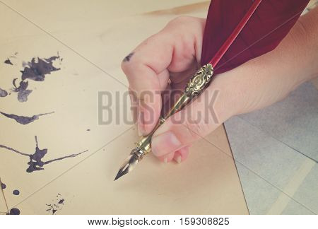 someone hand holding red feather pen over old papers with ink stains, retro toned