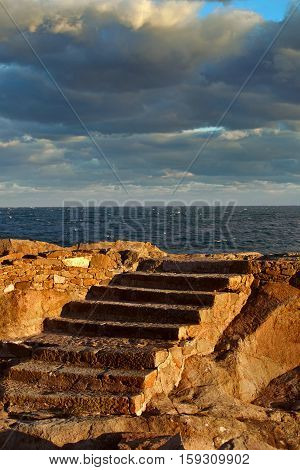 Seascape. Rock against the sea on a sunny day. A stone staircase carved into the rock. Stairs old old. Against the background of gloomy sky rock. Through the clouds of sunlight breaks and falls on stairs