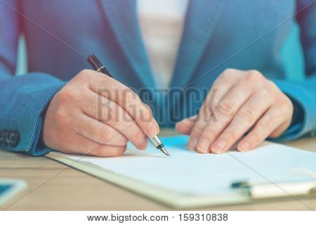 Close up of female hands writing signature on business agreement contract in the office
