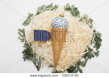 Colorful Christmas or New Year decoration with white blue christmas ball ice cream cone blue tag with rose thread and tree branch on white background