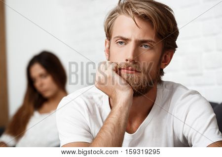 Upset young handsome man in quarrel with his girlfriend on sofa background.