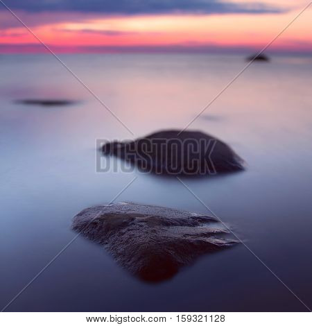 Beautiful seascape at sunset. In the foreground is a large stone. Bokeh. Long exposure.