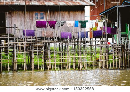 Traditional wooden houses on Inle lake with drying colorful clothes Myanmar (Burma)