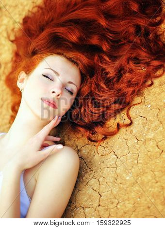 Beautiful young woman portrait with long curly rude hair and perfect fresh skin lying on the dried up ground with cracks, closed eyes, skin and hair care concept, dryness and moisture