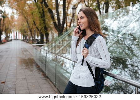 Cheerful lovely young woman with backpack standing and talking on cell phone in park