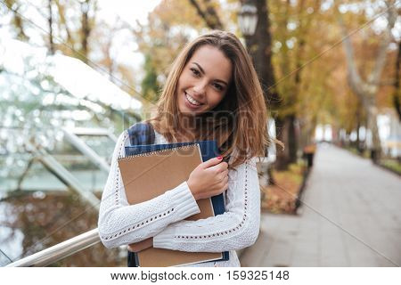 Smiling cute young woman with notebooks standing in park