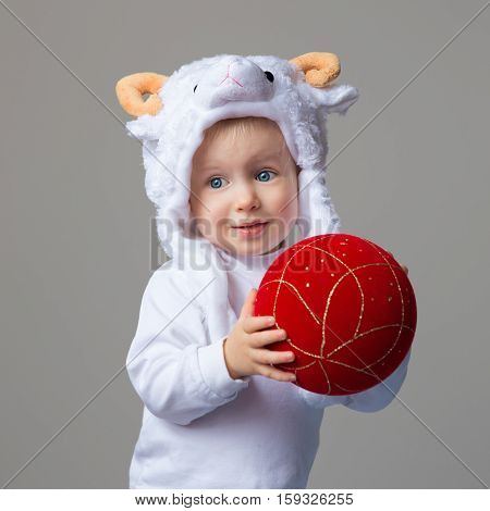 Portrait of smiling Caucasian baby with blue eyes wearing a sheep hat with horns and white shirt standing on a light background holding red golden chinese ball New Year concept studio