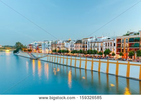 View of urban embankment in Seville along the Guadalquivir river at sunset. Spain. Andalusia.
