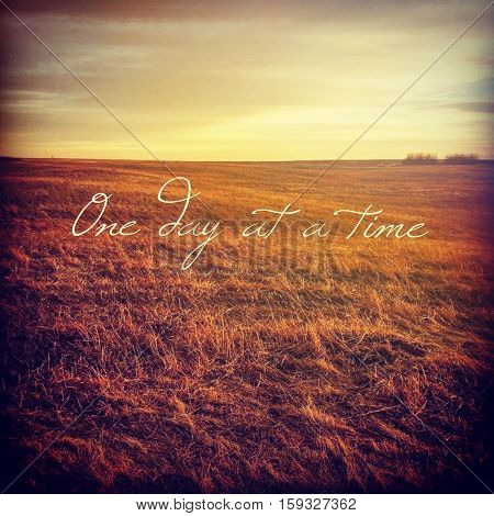 Inspirational quote on scenic field landscape with bright sky, orange grass and isolated bushes at sunset.  Peaceful prairie sunset field landscape view. Bright sky. Instagram effects.