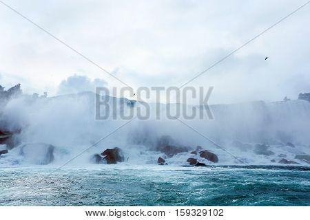 flowing water into ocean at waterfall in fog