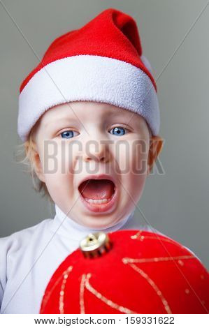 Closeup portrait of Caucasian baby with blue eyes wearing a Santa hat on light background holding red golden chinese ball decoration screaming in fear surprise New Year concept