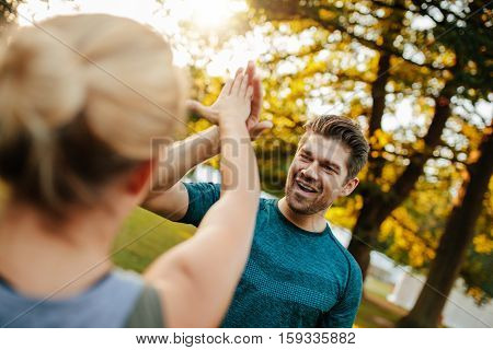 Fit Young Man Giving High Five To Woman
