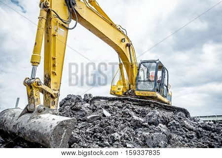 Yellow excavator is making pile of soil by pulling ground up on heap at construction site project in progress.
