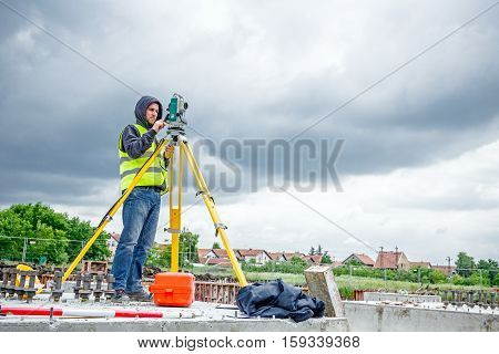 Zrenjanin Vojvodina Serbia - May 28 2015: Surveyor engineer is measuring level on construction site. Surveyors ensure precise measurements before undertaking large construction projects.