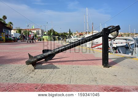 Lavrion Greece - Sept 18 2016: Big vintage anchor on the seafront in small town Lavrion in Attica. Greece very popular place of destination for spending time during vacation