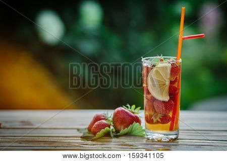 Glass of cold tea with mint, strawberry, lemon, on table, on green background