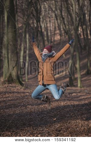 Active woman jumping outdoor in forest