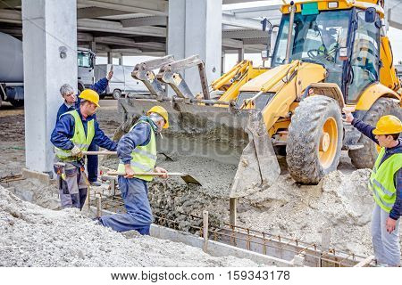 Zrenjanin Vojvodina Serbia - May 28 2015: Workers are filling out with concrete armored shape hole in ground using shovels.