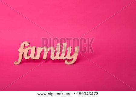 Word family, wooden letters on pink paper background with free space for text. Love and unity concept