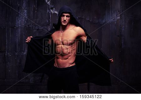 Mid shot portrait of brutal sexy male with bristle on face who is taking off a hoodie. Looking at the camera while posing over black background