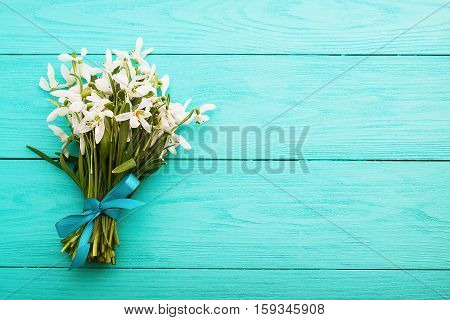 Fresh bouquet of flowers and silk ribbon on blue wooden background. Mothers day. Top view