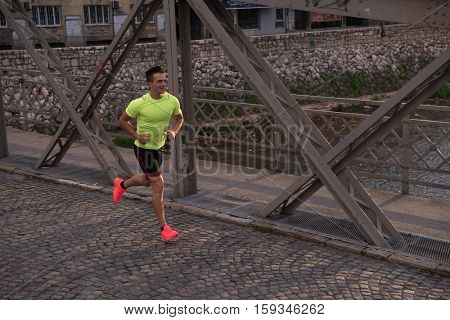 Young sporty man running on sidewalk at early morning jogging with city sunrise scene in background
