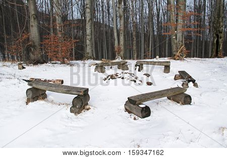 circle of several wooden benches around the fire place on the edge of forest in winter