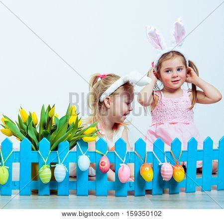 Happy little girls playing with Easter decoration eggs