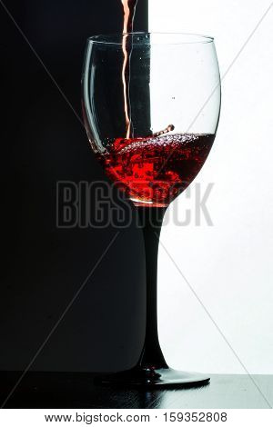 Red wine pouring. on a black background. alcohol