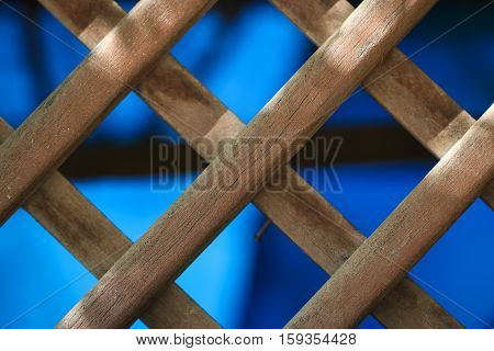 Background of brown wooden lattice fence pattern.