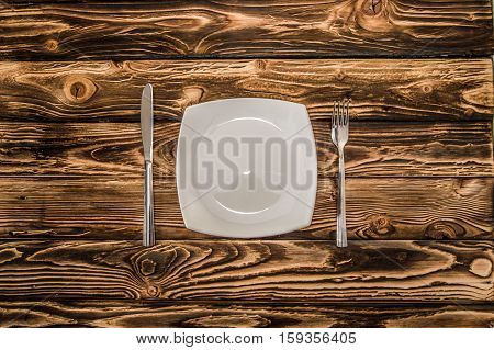 cutlery - fork, knife and spoon on a wooden table