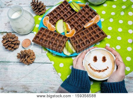 Cappuccino coffee with smiley face with waffles on wooden table in female hands overhead view