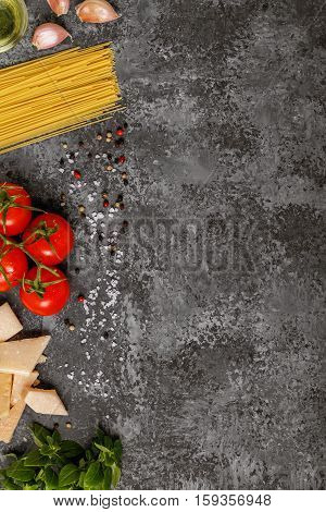 Italian food cooking-tomatoes basil pasta olive oil and cheese on stone backroonde top view copy space.