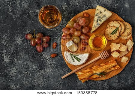 Assortment of cheese with wine honey nuts and grape on a cutting board top view.
