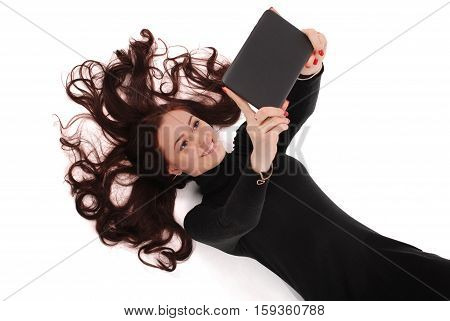 Happy student teenage girl lying on the floor looking at tablet pc isolated on white