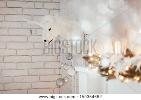 Christmas decorations with white unicorn and candlestick in white living room. Burning lantern and christmas tree