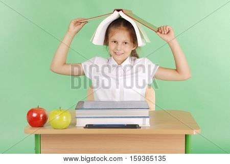 Education people children and school concept - young school girl sitting at a desk with a book on her head over green