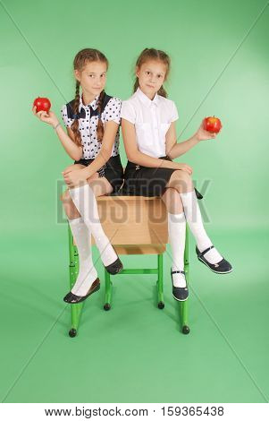 Two girls in a school uniform sitting on desk and eat apples isolated on green
