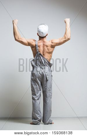 young handsome muscular construction worker in overalls, on a light background